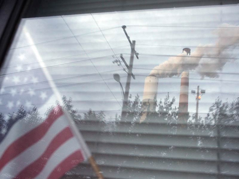 A coal-fired power plant in Pennsylvania, reflected in a neighboring home's window.