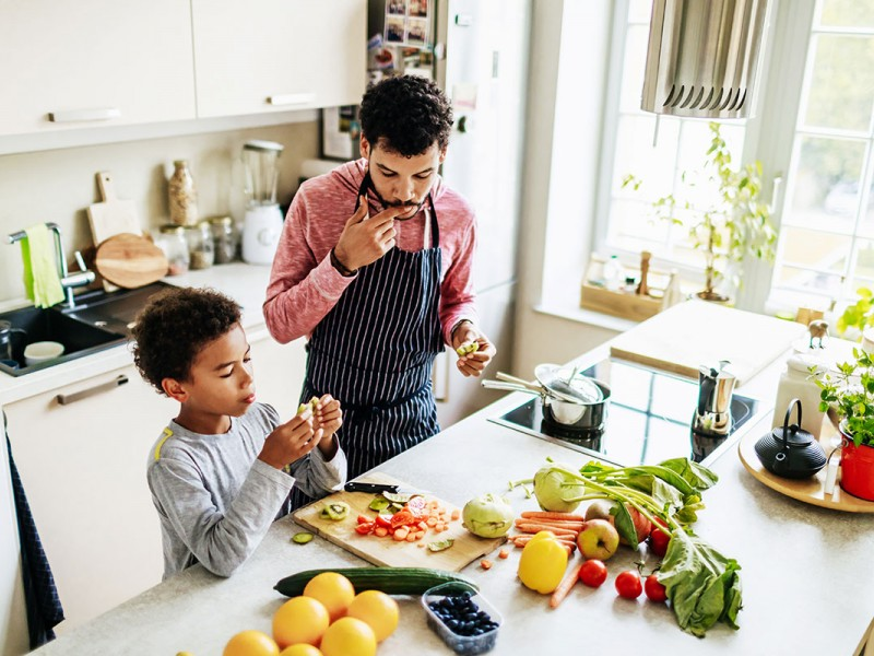 A father prepares a meal with his son on an induction stove.