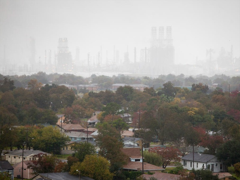 An oil refinery looms over Port Arthur, TX. People of color are nearly twice as likely as white Americans to live within a fenceline zone of an industrial facility.