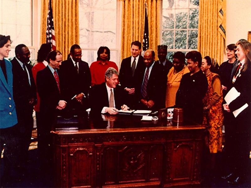 President Clinton signs the Executive Order in the Oval Office (February 11, 1994).
