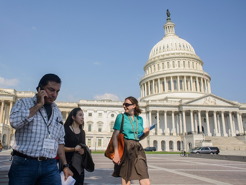 Mario Vargas, a farmworker organizer from Ohio, his daughter Myra Vargas (middle), and Alexis Guild of Farmworker Justice walk past the U.S. Capitol in July of 2013, as they head to a meeting in the Hart Senate Office Building.