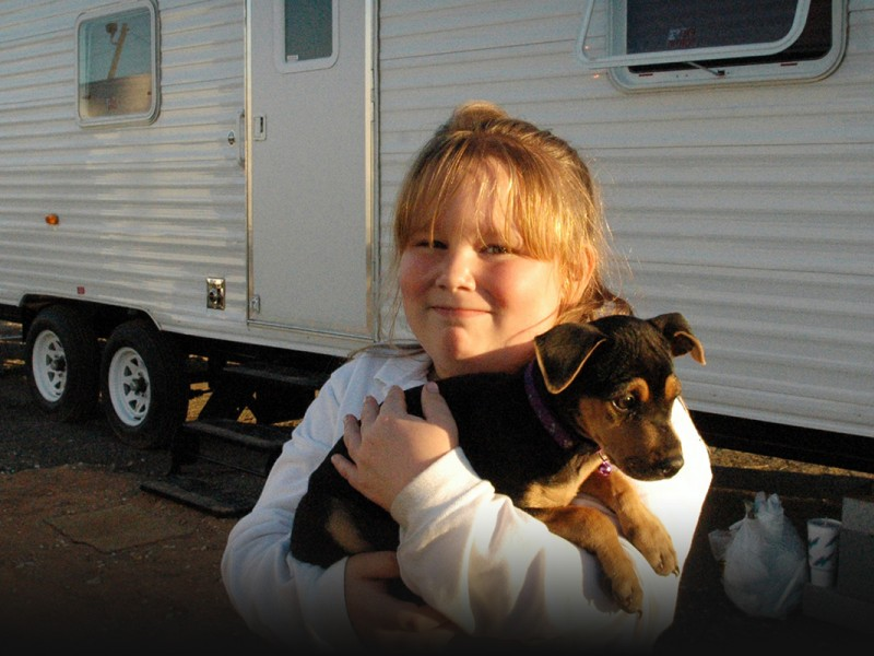 Brianna Edson, a Mississippi resident, and her new dog Dixie in front of the travel trailer serving as their temporary home along with Brianna's mother Wendy (not pictured) at the Ingalls-Wright Emergency Group Site, in November 2005.