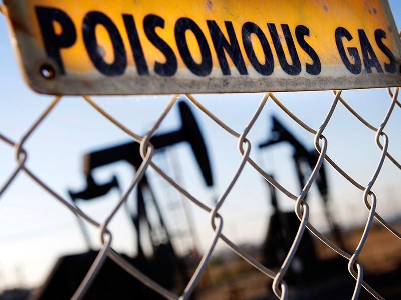 A sign hangs by the Inglewood Oil Field in Los Angeles, warning of hazardous fumes.
