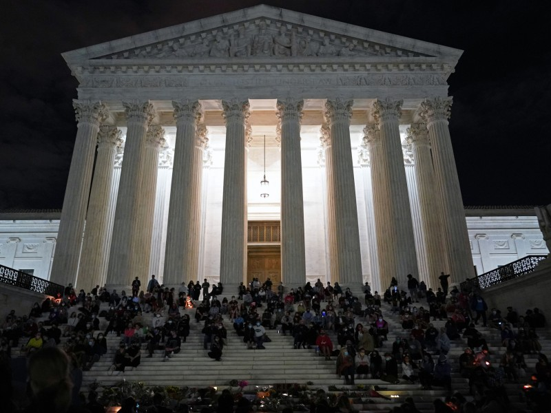 Photo of people gathered at a makeshift memorial for late Justice Ruth Bader Ginsburg on the steps of the Supreme Court building in Washington, D.C., on September 18, 2020.