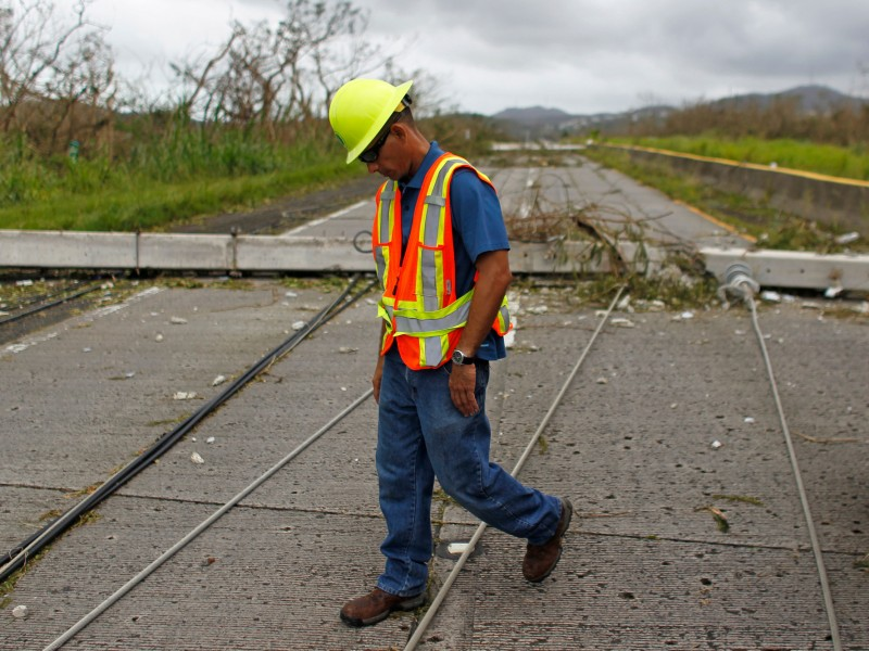 A Puerto Rico Power Authority worker walks between downed power lines in the aftermath of Hurricane Maria in Luquillo, Puerto Rico, Thursday, September 21, 2017.