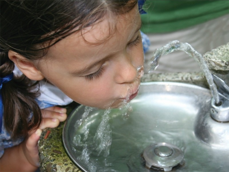 A girl drinks from a water fountain.