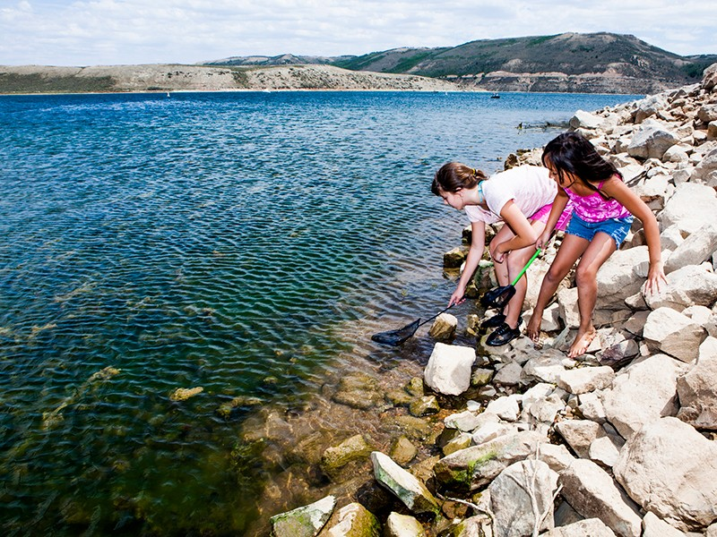 Young girls play near a river. Section 401 of the Clean Water Act empowers states and tribes to assess the impacts of federal projects on rivers, lakes, streams, and wetlands within their borders.