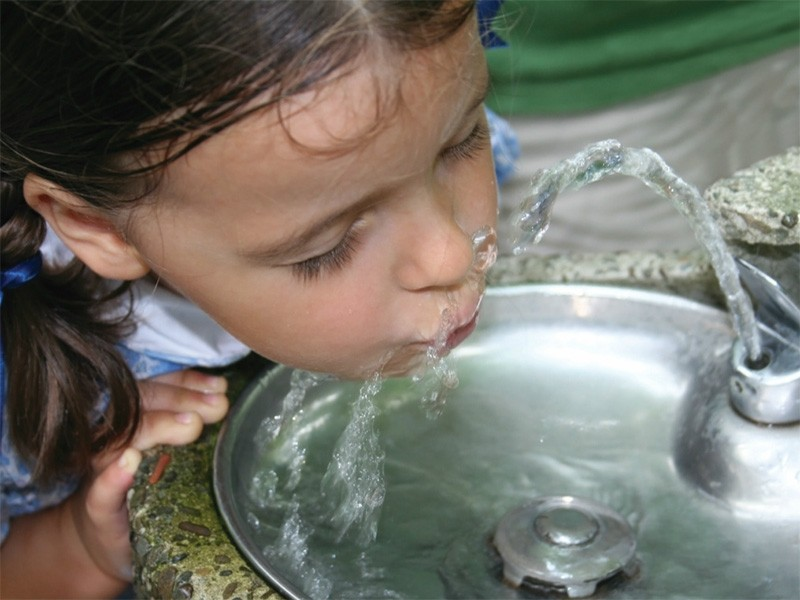 A child drinks from a water fountain.