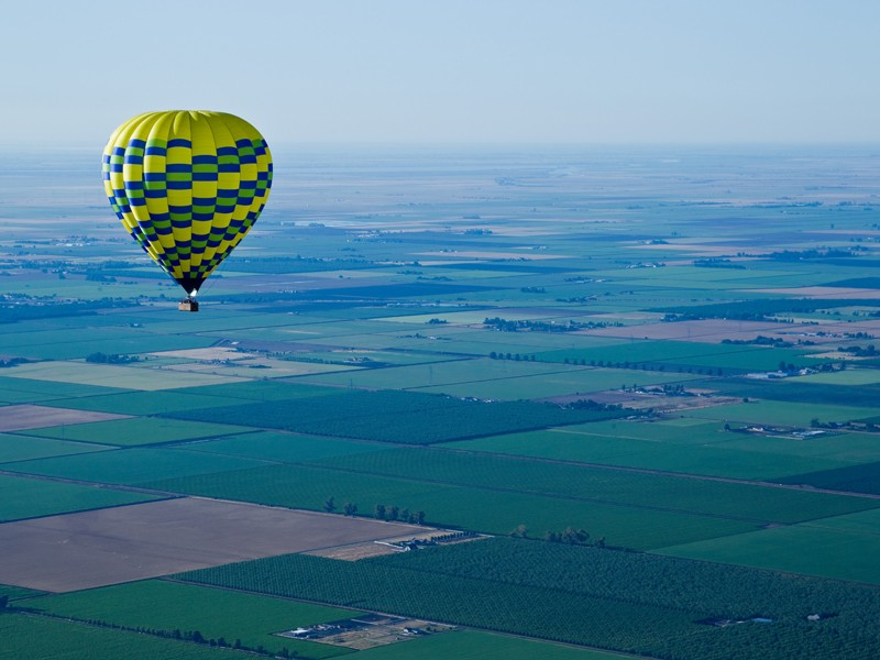 A hot air balloon floats before the smoggy backdrop of California's Central Valley outside of Sacramento.