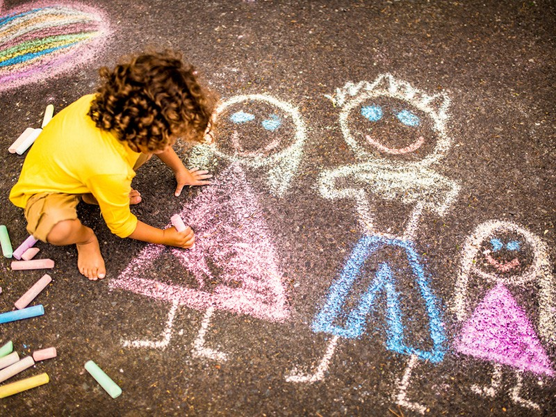 A child draws with chalk.