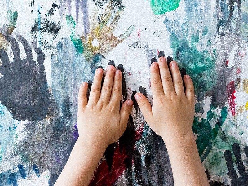 A child paints handprints on the wall.