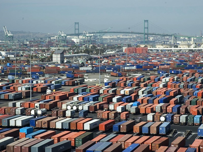 A rail line runs past shipping containers at the Port of Long Beach.