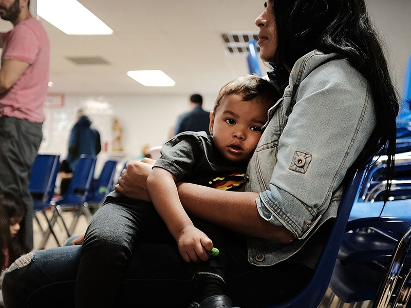 A woman who identified herself as Jennifer sits with her son Jaydan at the Catholic Charities Humanitarian Respite Center after crossing the U.S.-Mexico border in McAllen, Texas.