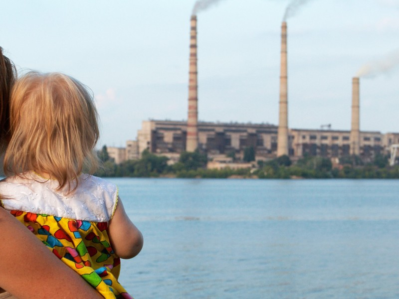 A mother and child near an industrial plant.