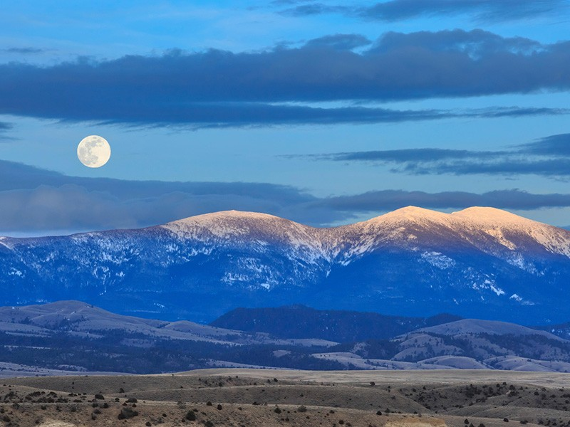 A full moon is seen above Mount Baldy in the Big Belt Mountains near Townsend, Montana, April 2019. Nearby land was recently protected by a federal judge ruling; however, the Big Belt Mountains are still at risk.