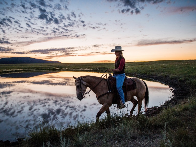 A bird researcher rides past water on a ranch in Montana.