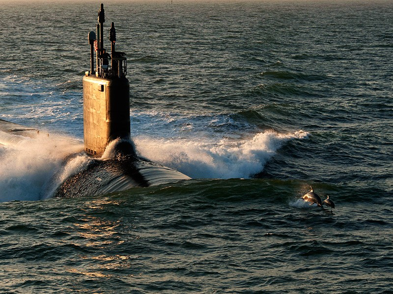 Dolphins swim in advance of Virginia-class attack submarine PCU Minnesota.