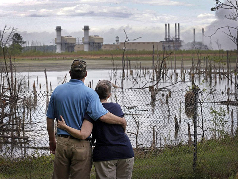 A couple in Dukeville, N.C., looks across a coal ash pond full of dead trees.