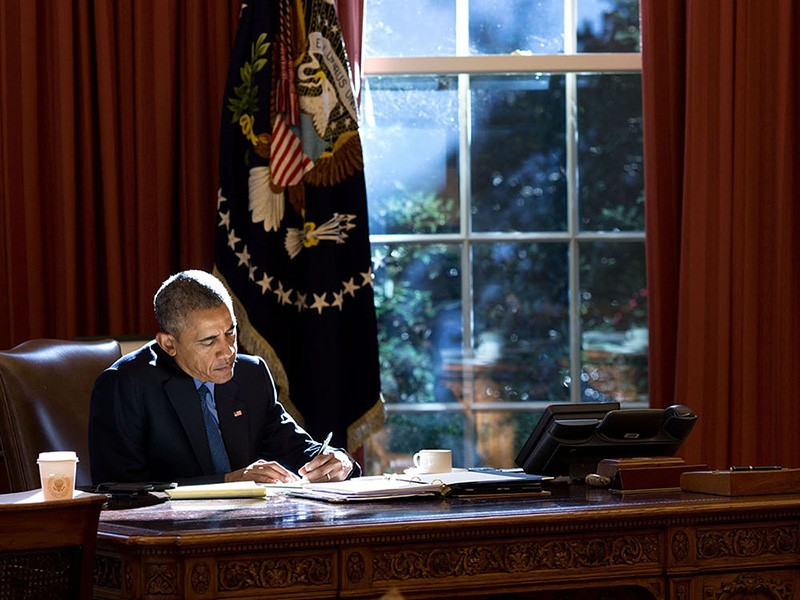 Afternoon autumn light bathes the President as he works at the Resolute Desk in the Oval Office.