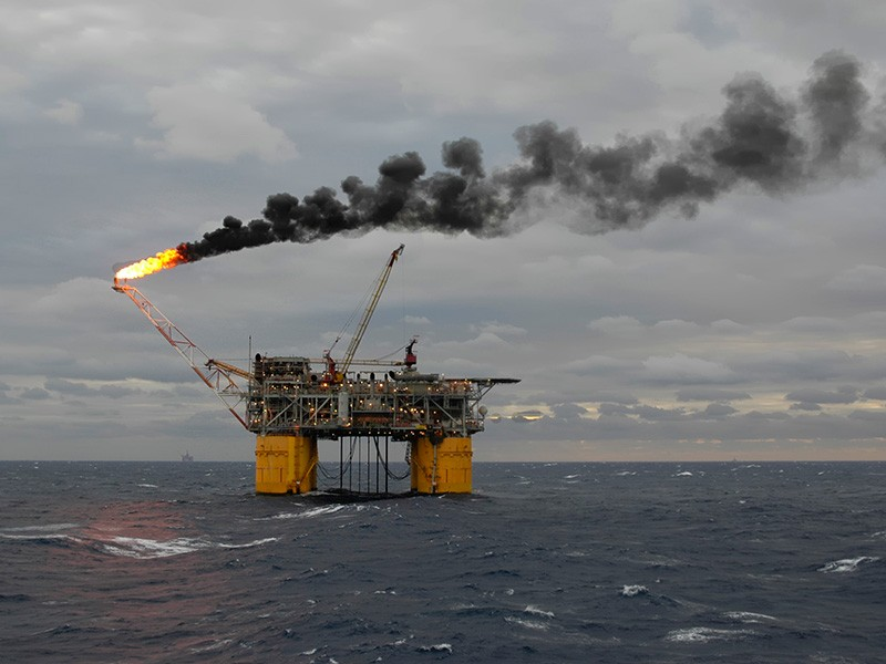 A tension-leg oil production platform burns off unrecoverable gas and leaves a plume of smoke in the Gulf of Mexico.