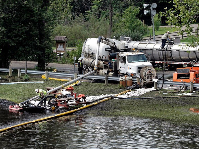Workers using suction hoses try to clean up an oil spill of approximately 800,000 gallons of crude oil from the Kalamazoo River July 28, 2010 in Battle Creek, Michigan.