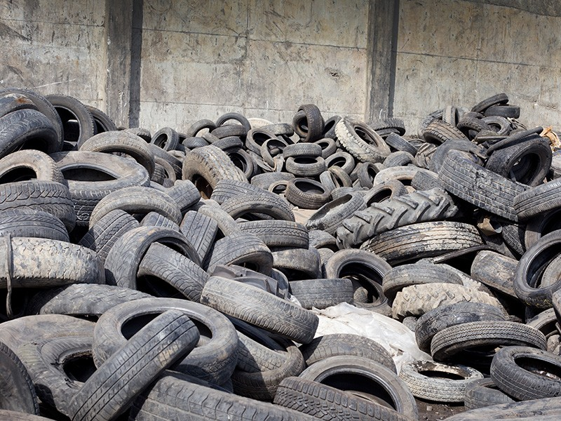 Old tires, stocked for recycling.