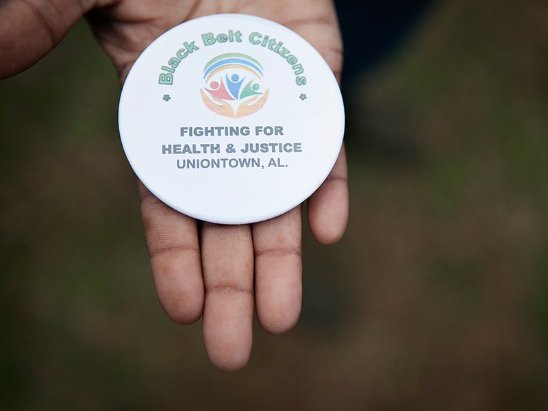 Client Esther Calhoun holds a button from the local community group fighting coal ash pollution in Uniontown, AL.