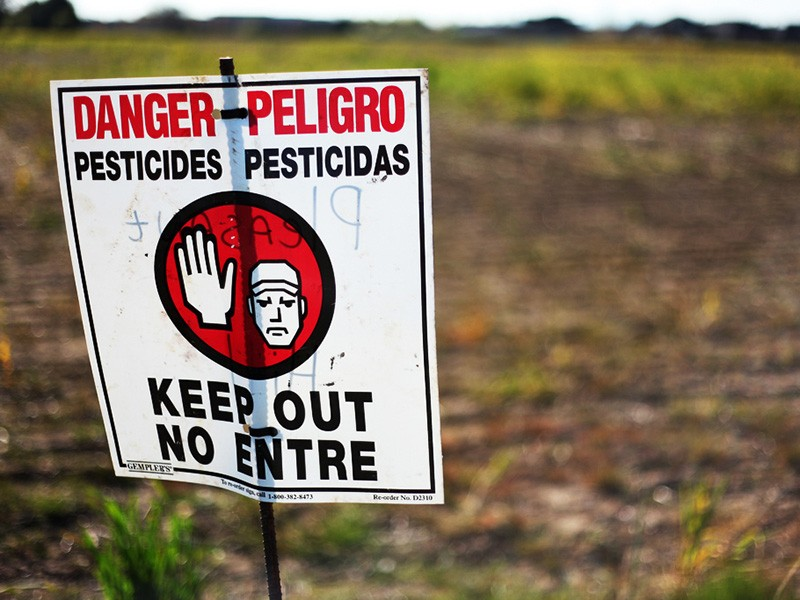 A sign warns of pesticide application in a farm field.