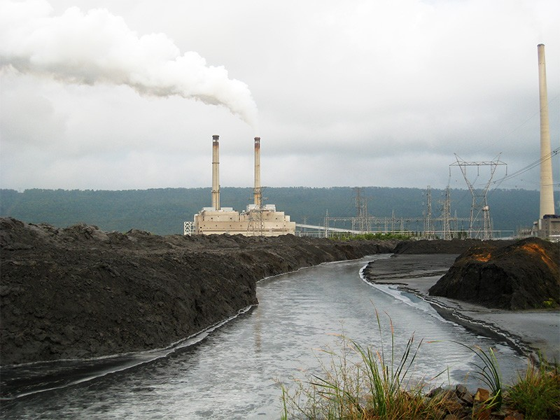A power plant located next to a waterway.