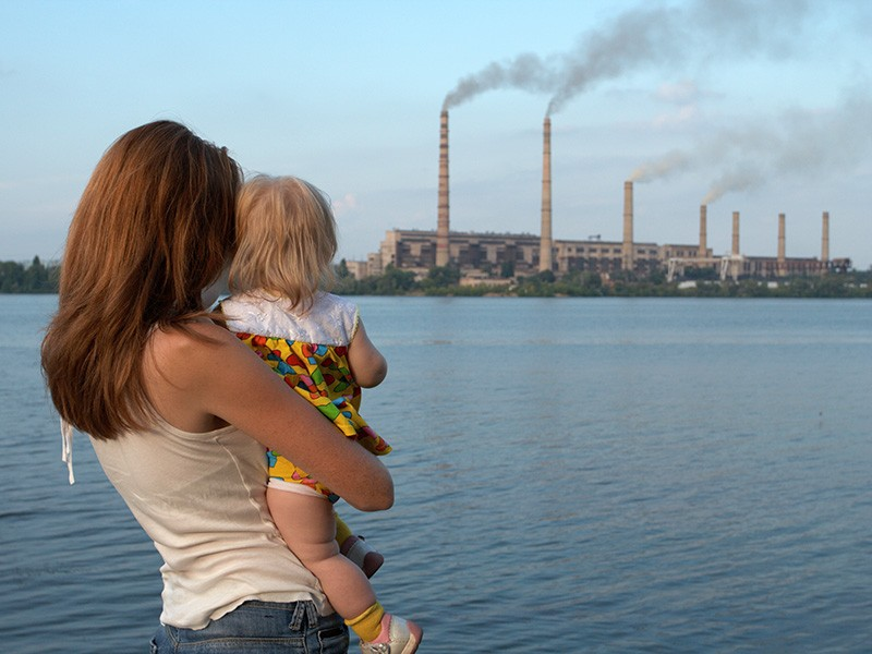A woman and child watch a power plant across a lake.