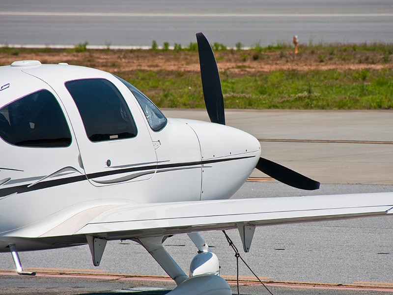 A small private plane tied down next to the runway at a regional airport.