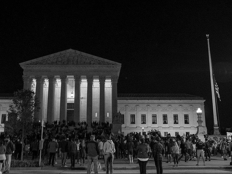 The national flag flies at half staff as people gather to mourn the passing of Supreme Court Justice Ruth Bader Ginsburg at the steps \of the Supreme Court on Sep. 18, 2020, in Washington, D.C.