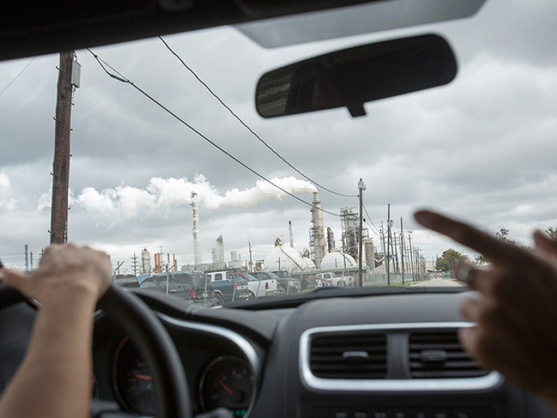 """Photo of a polluting oil refinery through the windshield a car leading a """"toxic tour"""""""