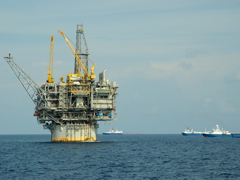 A seismic survey fleet passes an off-shore oil rig in the Gulf of Mexico.