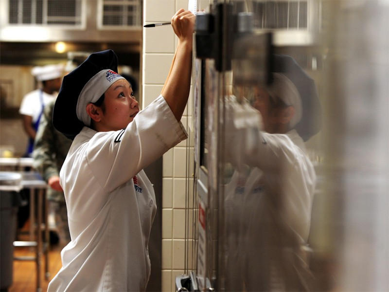 A food service specialist with the 55th Force Support Squadron marks down the exact temperature of one of three walk-in freezers at a dining facility.