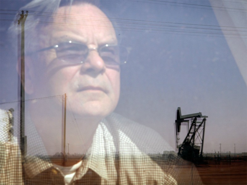 Walt Desatoff looks out the window of his bedroom at the oil field across the street from his home in Shafter, CA. A few years ago, the field was filled with roses. Now, Desatoff sees multiple oil pumpjacks and a giant flare.