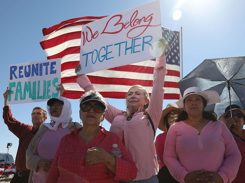 "Activists stand in front of a U.S. flag, holding signs that say ""We Belong Together"" and ""Reunite Families"" in protest of family detentions outside of the Tornillo Port of Entry in Tornillo, TX."
