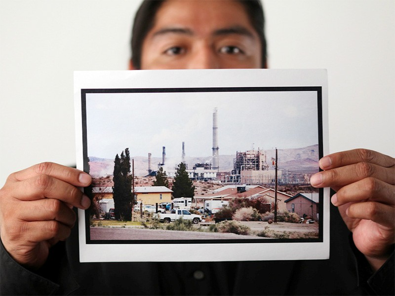 Moapa Band of Paiutes Tribal Chairman William Anderson holds a photo of the Reid Gardner Power Station.