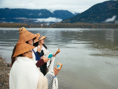Members of the Tulalip Tribe sing along the banks of the Fraser River in Chilliwack, British Columbia, as part of a ceremony to honor the waters and marine life so integral to the Coast Salish way of life.
