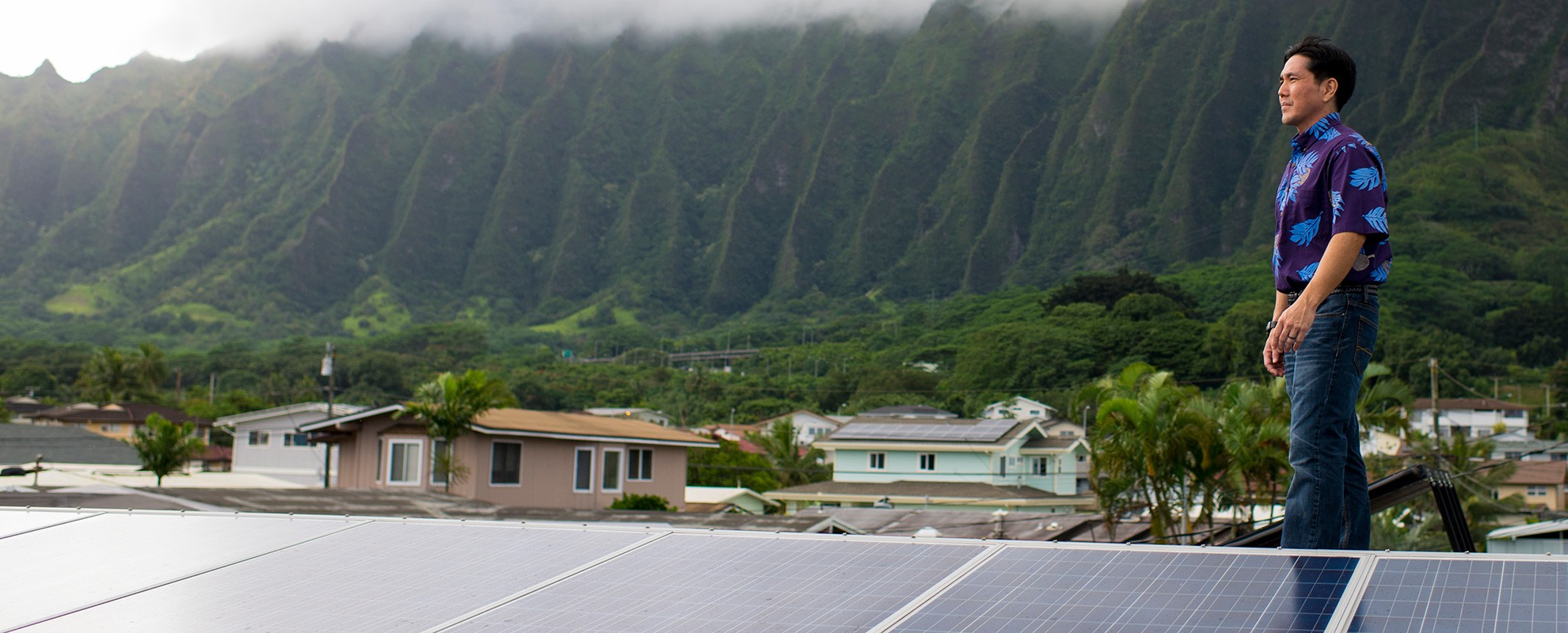 Attorney Isaac Moriwake stands next to solar panels installed on his rooftop in Hawai'i.