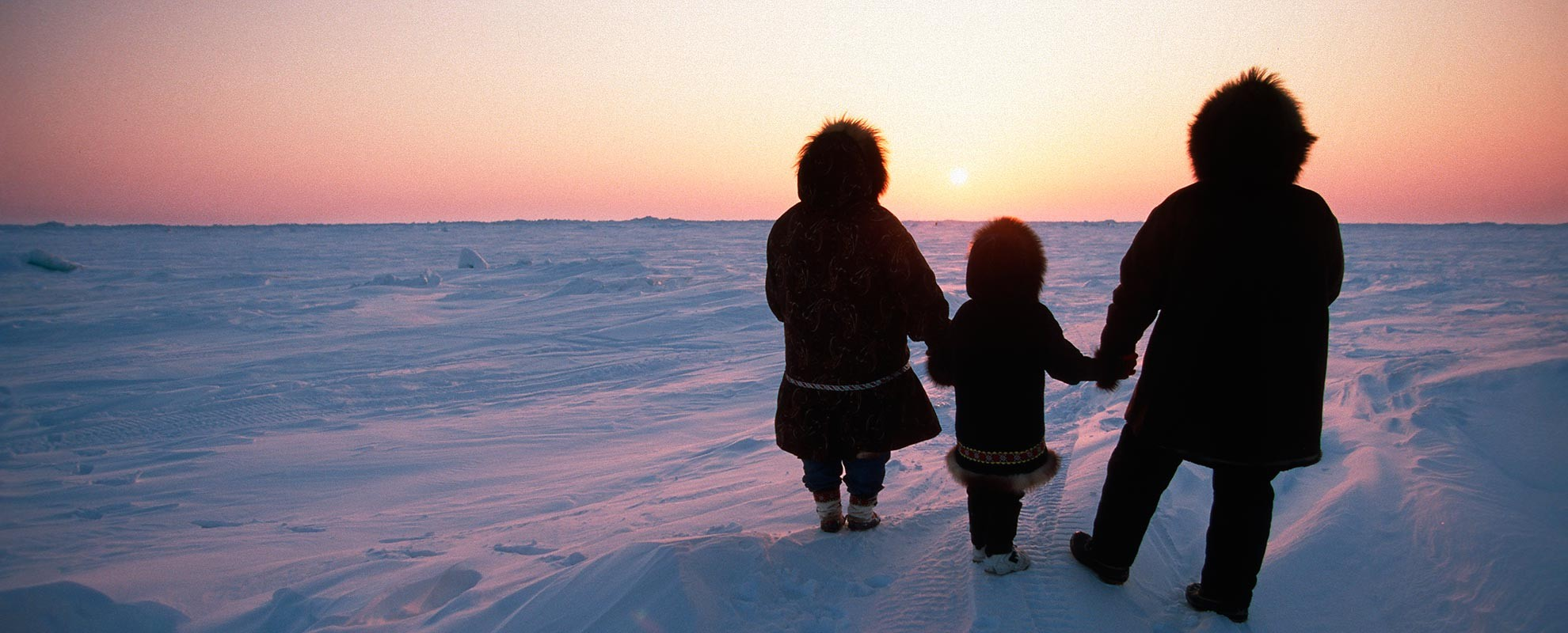 Family framed against the sunset, in the Arctic.