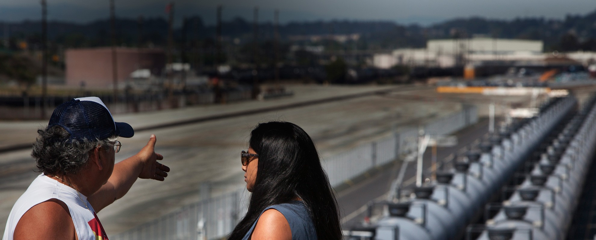 Communities for a Better Environment Organizer Andrés Soto and Earthjustice Attorney Suma Peesapati look over the railyard in Richmond, where highly explosive and toxic crude oil is being brought into the city.