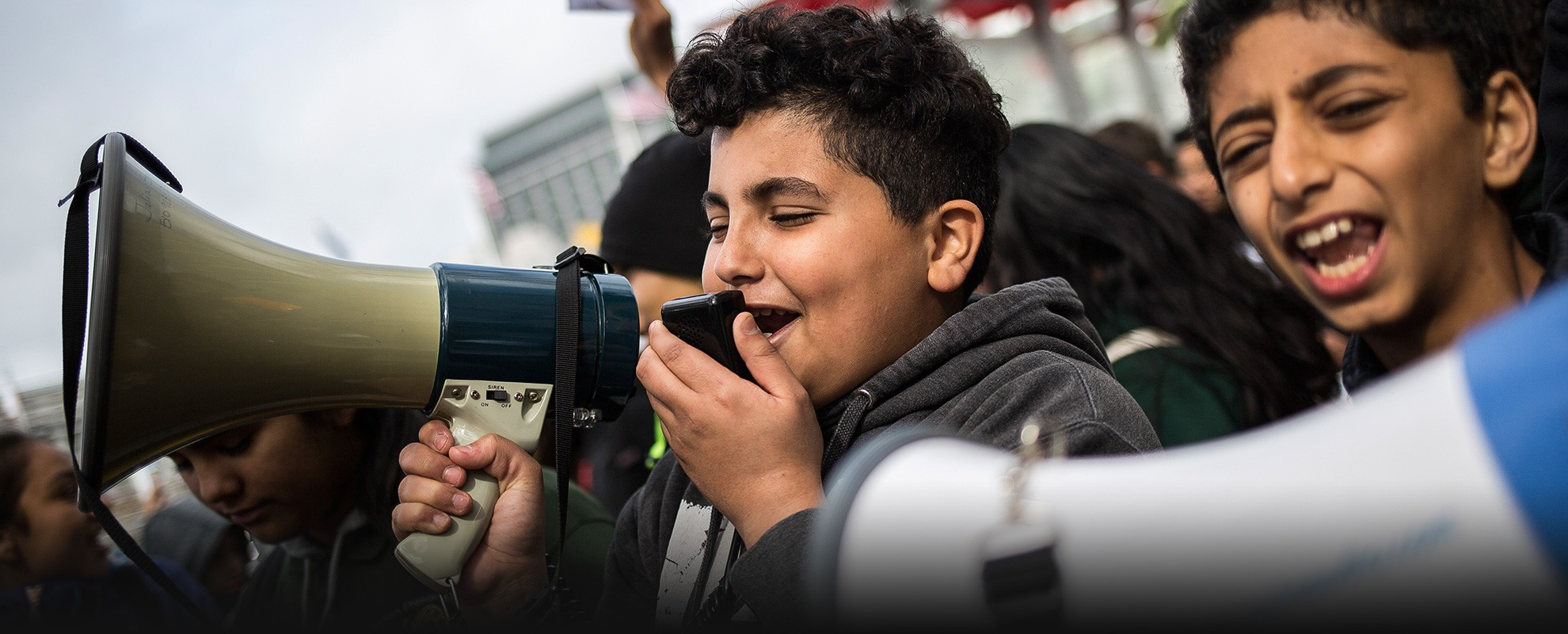 Adam Abdo Alshuga (right), 11-years-old, marches alongside Zakaria Homran, 13-years-old, with a megaphone.