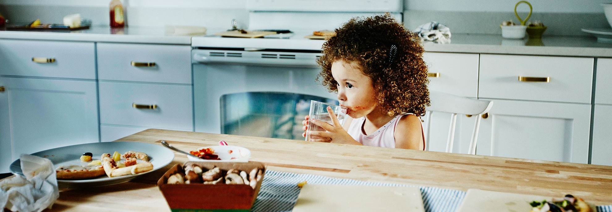 A young girl drinks a glass of water during snack time.