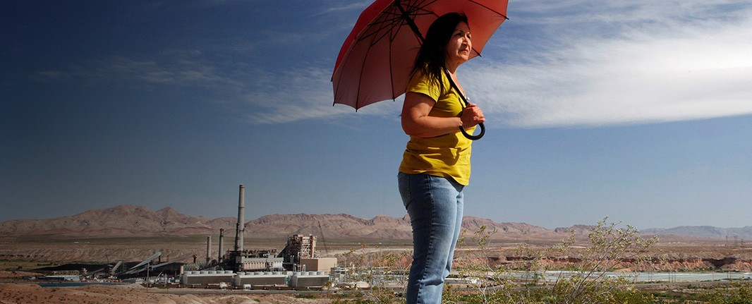 Vickie Simmons stands in between the Reid Gardner Power Plant and her house on the Moapa River Reservation.
