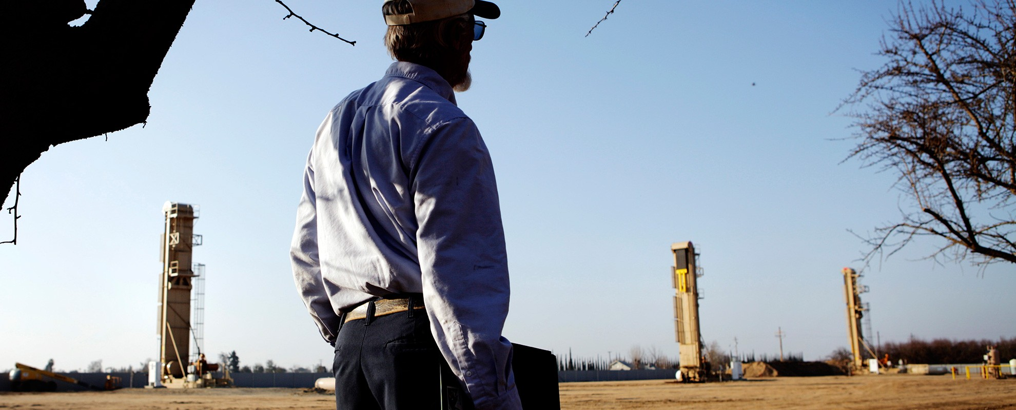 An almond farmer watches oil wells that have sprouted next to almond orchards near Bakersfield, CA.