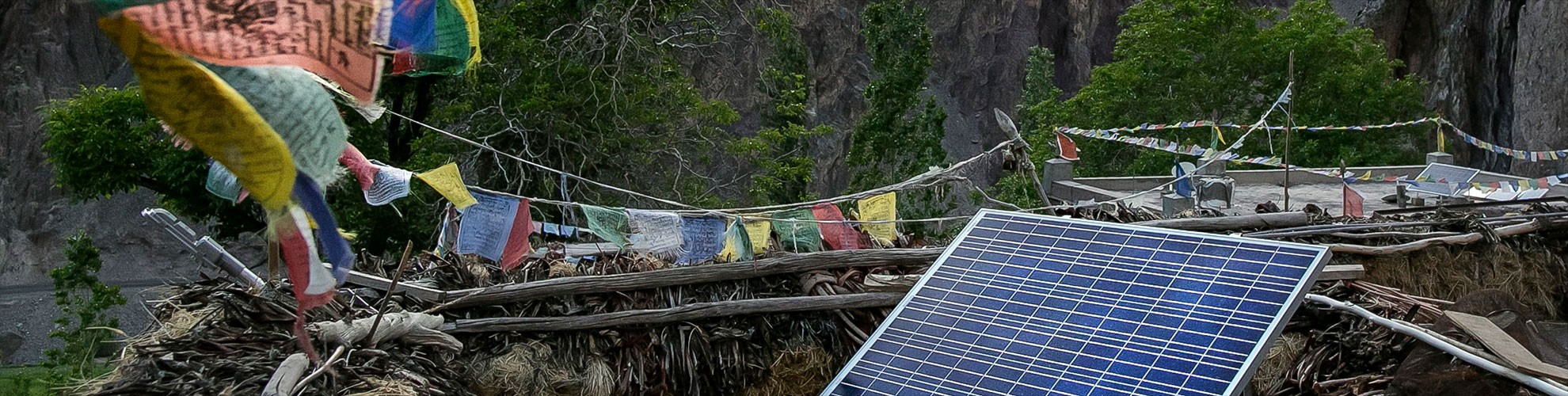 Prayer flags fly over rooftop solar panels. Renewables can bring energy to regions without traditional energy infrastructure.