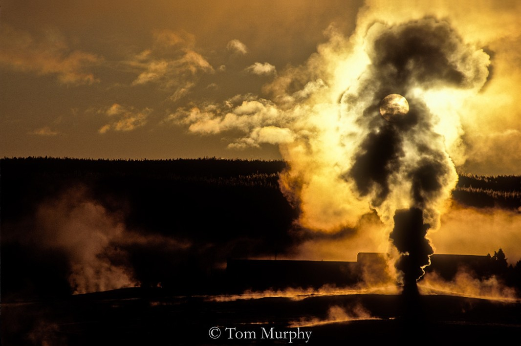 Puffs of steam from the Old Faithful geyser cone moved up and covered the early gold sun rising above the distant ridge.