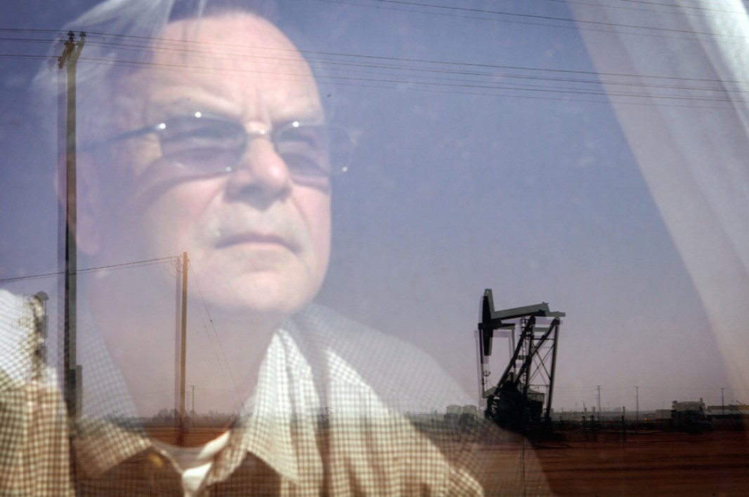 Walt Desatoff looks out the window of his bedroom at the oil field across the street from his home in Shafter, California. A few years ago the field was filled with roses. Now Desatoff sees multiple oil pumpjacks and a giant flare.