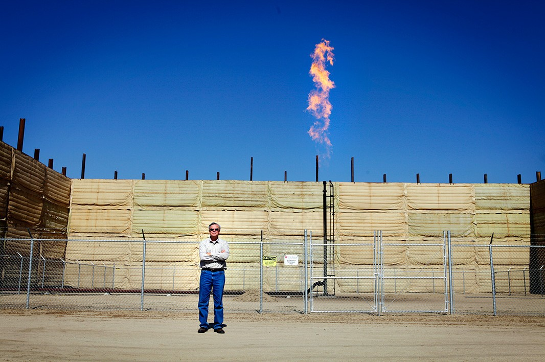 Walt Desatoff stands in front of a flare in an oil field next to his home.